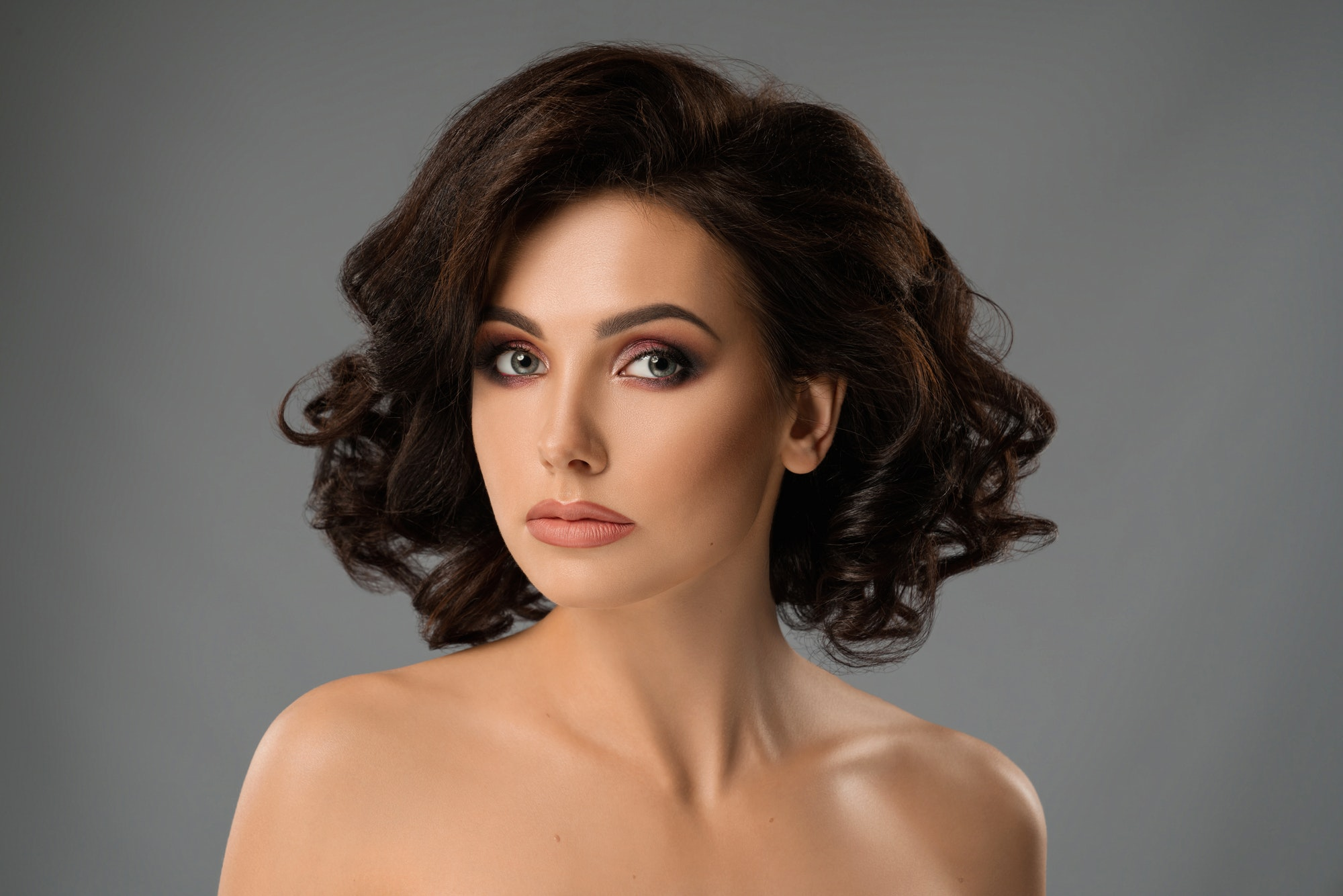 Beautiful brunette with stylish make up looking at camera