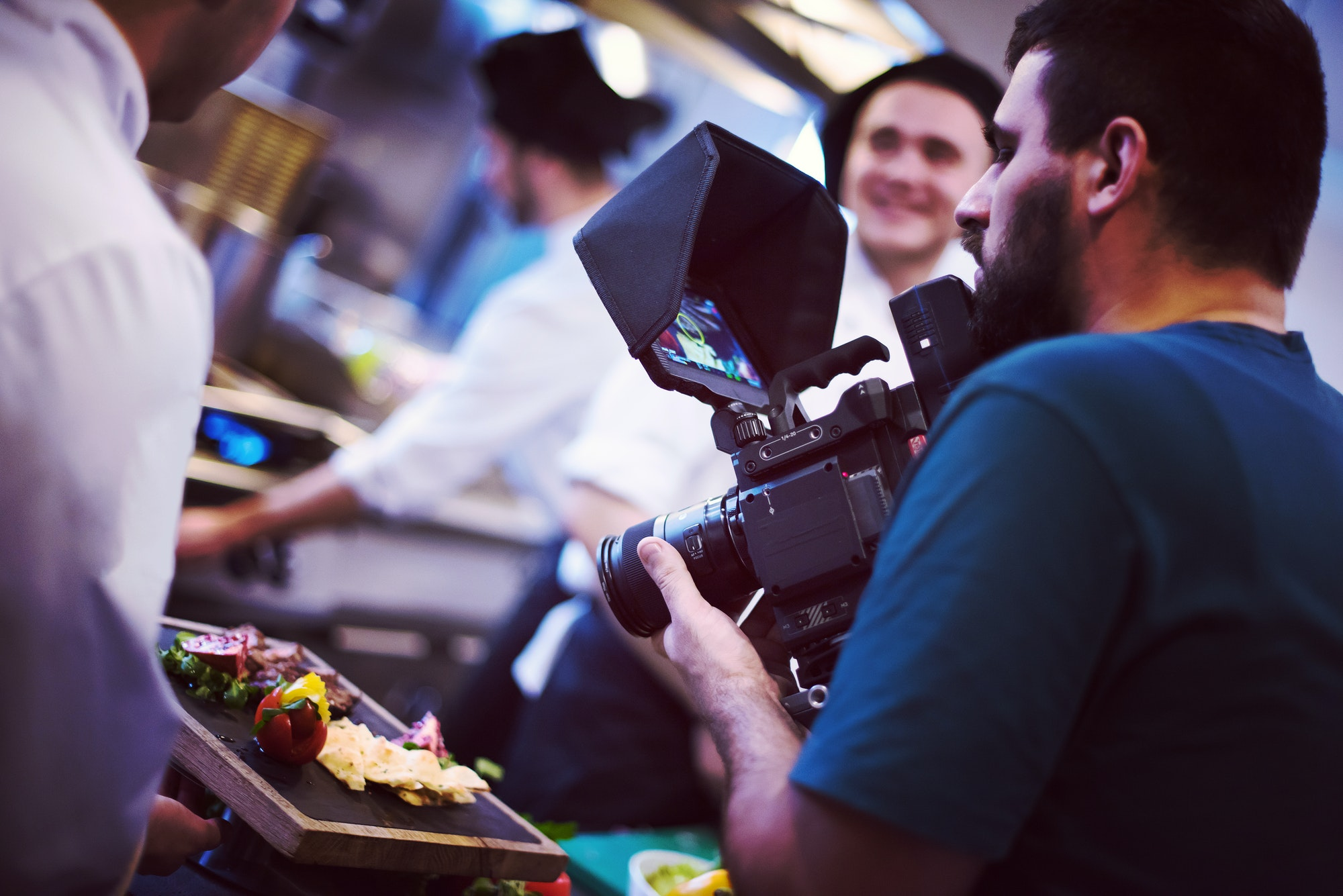 Gladlii videographer recording while a cook and chef prepare meal